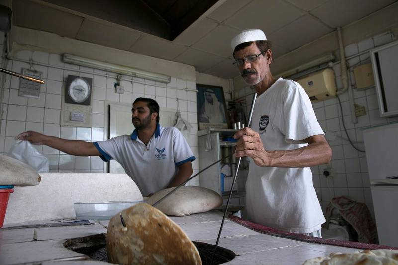 ABU DHABI, UNITED ARAB EMIRATES, May 5, 2015:   (R) Kashmiri baker Ghulam Fareed, 51, prepares fresh flat bread for a customer as he and his assistant work away a hot Spring afternoon at his brother's bakery, the Mohammed Murid Abdul Karim bakery in central Abu Dhabi. (Silvia Razgova / The National)  (Usage: May 5, 2015, Section: RV, Reporter: Zaineb al Hassani *** Local Caption ***  SR-150505-bakeries08.jpg