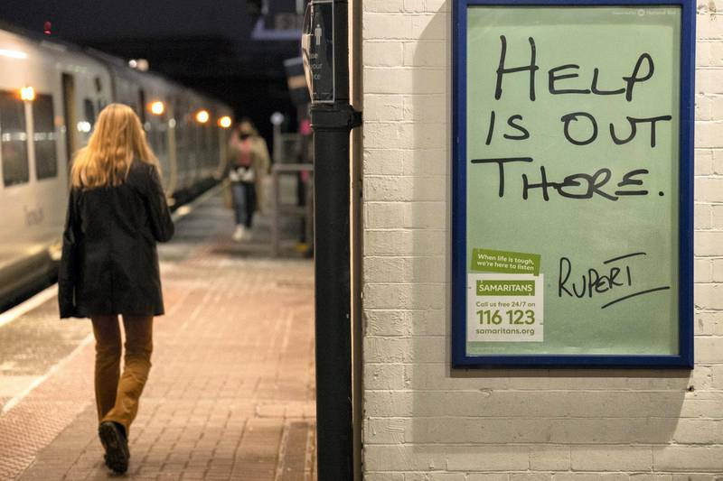 A female rail traveller walks along the platform at Loughborough Junction railway station where a Samaritan's poster urges those with mental health issues, or even thoughts of suicide, to seek help from the registered charity aimed at providing emotional support to anyone in emotional distress, struggling to cope, or at risk of suicide throughout the United Kingdom and Ireland, often through their telephone helpline, on 27th February 2021, in London, England. (Photo by Richard Baker / In Pictures via Getty Images)