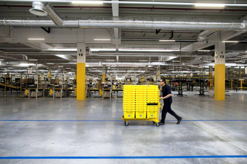 An employee pushes yellow product crates on a trolley across the work floor at the new Amazon Inc. fulfilment center on its official day of opening in Bielany Wroclawskie, Poland, on Tuesday, Oct. 28, 2014. The company announced on Monday that it's taking preorders for a streaming media stick that plugs into a TV, making it possible to watch a range of Internet video services. Photographer: Bartek Sadowski/Bloomberg