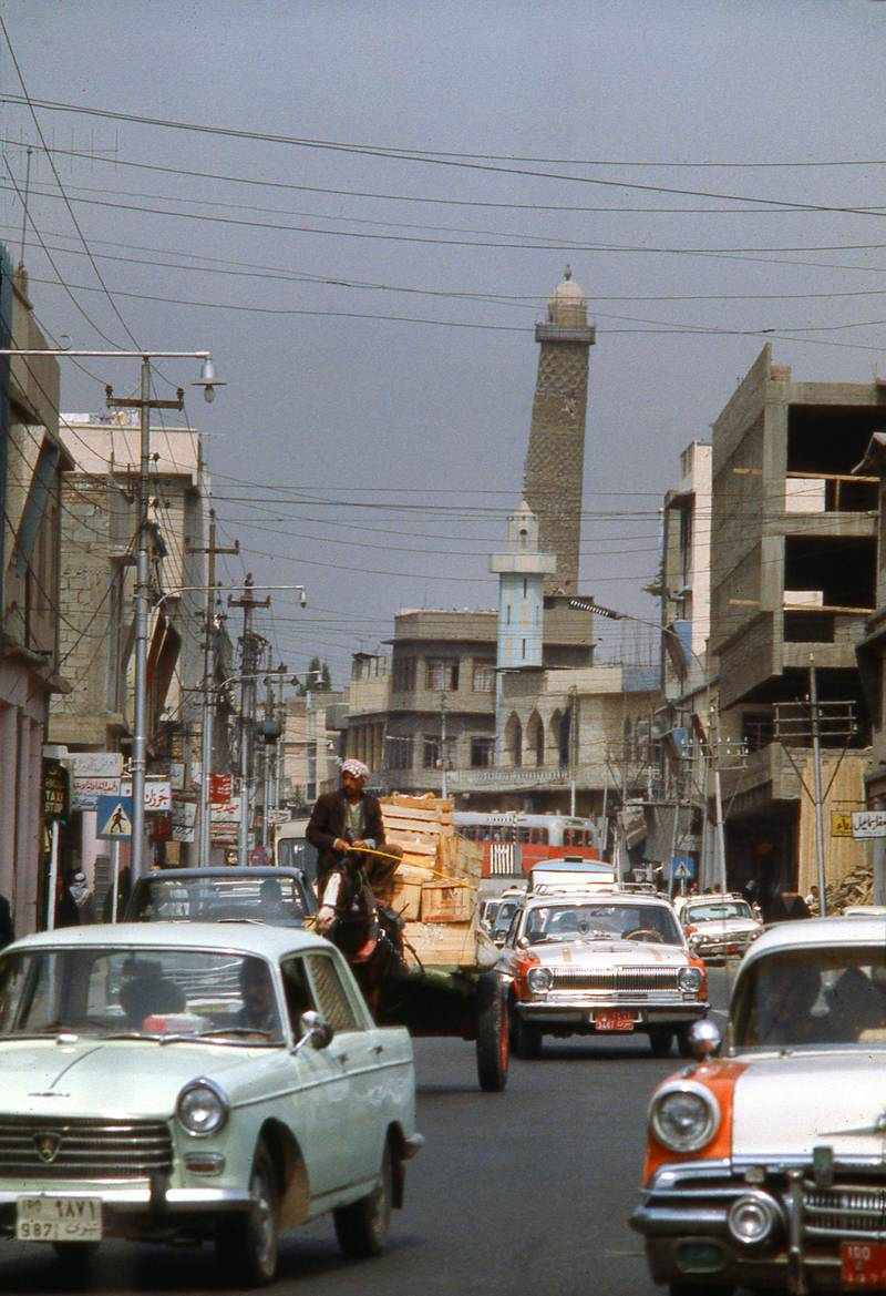 MOSUL - JANUARY 1 1978; Heavy traffic on street in downtown Mosul, largest city in Northern Iraq, with Leaning Minaret of the Great Mosque in the background, circa 1978 (Nik Wheeler/Corbis via Getty Images)