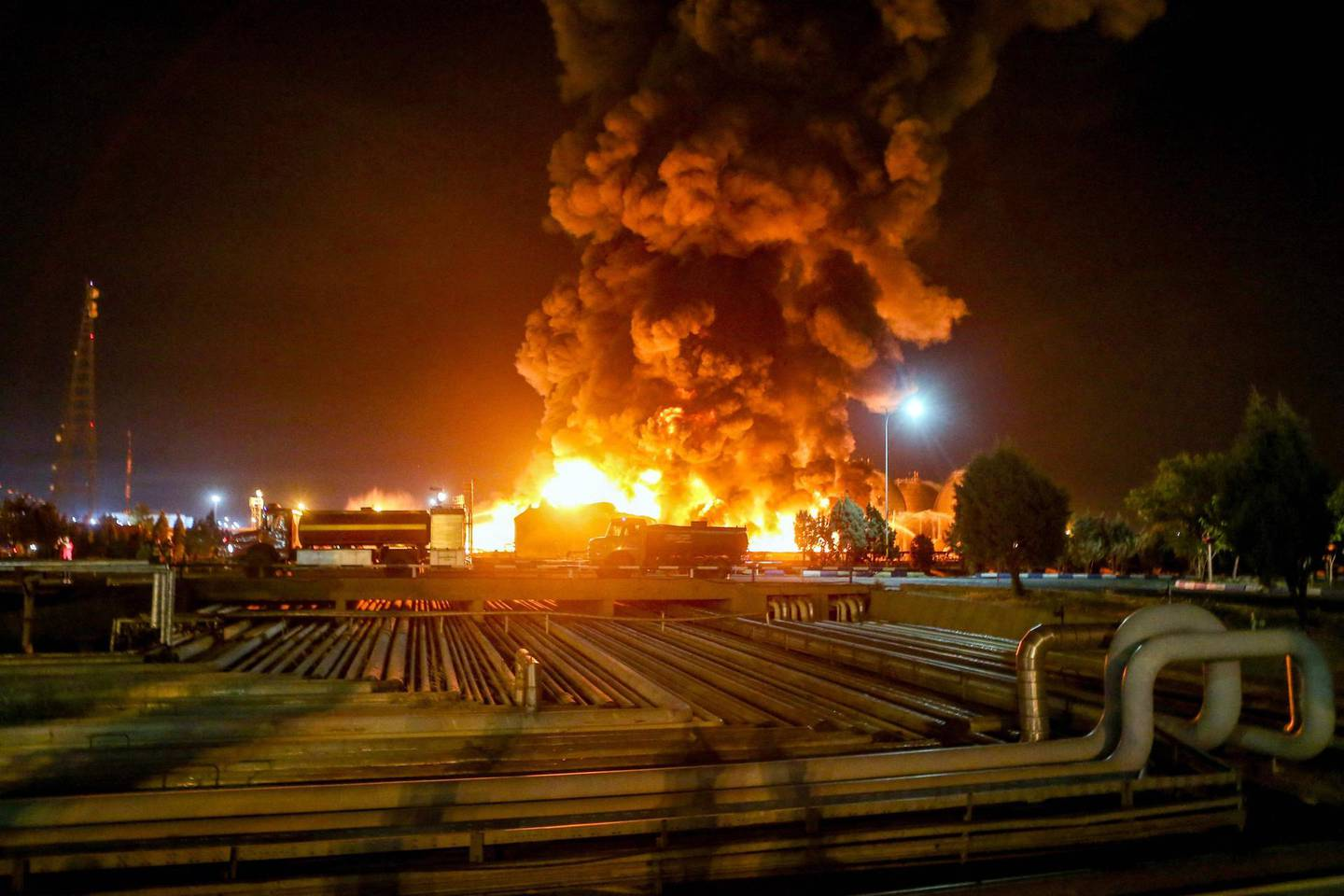 A picture taken late on June 2, 2021, shows fire raging at an oil refinery in the Iranian capital Tehran. A fierce blaze broke out at the refinery in southern Tehran after a liquefied gas line leaked and exploded, the head of the capital's crisis team said on state television. / AFP / TASNIM NEWS / Vahid AHMADI
