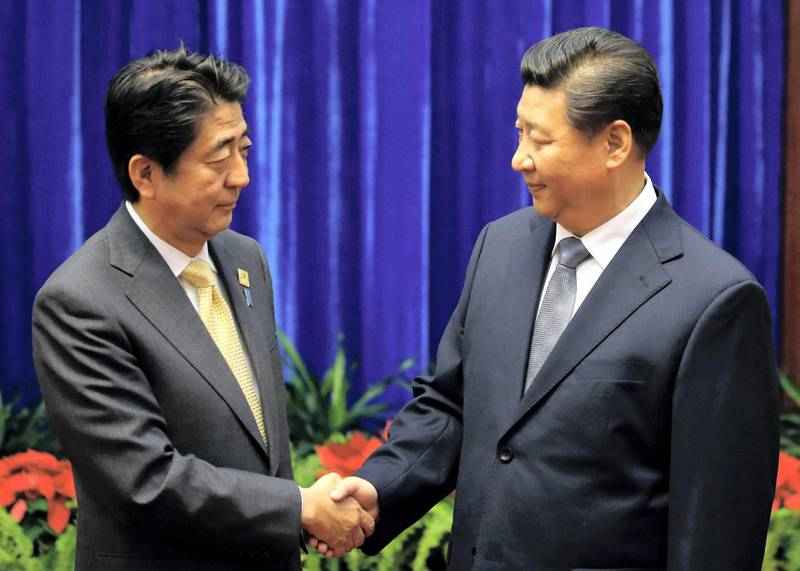 China's President Xi Jinping (R) shakes hands with Japan's Prime Minister Shinzo Abe (L) at the Great Hall of the People on the sidelines of the Asia-Pacific Economic Cooperation (APEC) Summit in Beijing on November 10, 2014. Top leaders and ministers of the 21-member APEC grouping are meeting in Beijing from November 7 to 11.    AFP PHOTO / POOL / Kim Kyung-Hoon / AFP PHOTO / POOL / KIM KYUNG-HOON