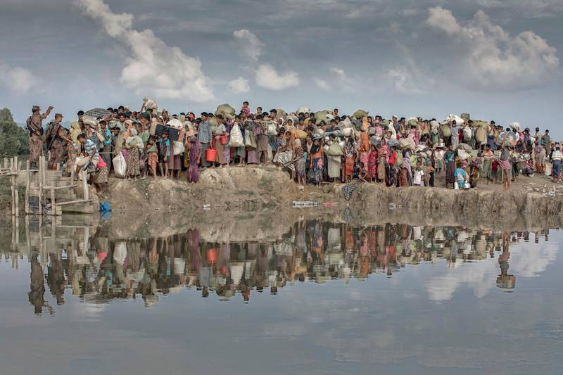 Rohingya refugees pack as they wait proceed to camps after crossing the Naf River border from Myanmar into Bangladesh on November 2, 2017 near Anjuman Para in Cox's Bazar. According to the United Nations High Commissioner for Refugees (UNHCR) more than 646,000 Rohingya refugees have fled from Myanmar on August 25, 2017 most of them trying to cross border reach Bangladesh.