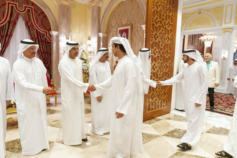 DUBAI, UNITED ARAB EMIRATES - May 19, 2019: HH Sheikh Mansour bin Zayed Al Nahyan, UAE Deputy Prime Minister and Minister of Presidential Affairs (2nd R), greets HE Obaid Humaid Al Tayer, UAE Minister of State for Financial Affairs (back 2nd L), during an iftar reception hosted by HH Sheikh Mohamed bin Rashid Al Maktoum, Vice-President, Prime Minister of the UAE, Ruler of Dubai and Minister of Defence (not shown), at Zabeel Palace. Seen with HH Sheikh Hamdan bin Mohamed Al Maktoum, Crown Prince of Dubai (R), HE Sultan bin Saeed Al Mansouri, UAE Minister of Economy (back L) and HE Mohamed Juma Al Naboodah (back 3rd L).  ( Mohamed Al Hammadi / Ministry of Presidential Affairs ) ---