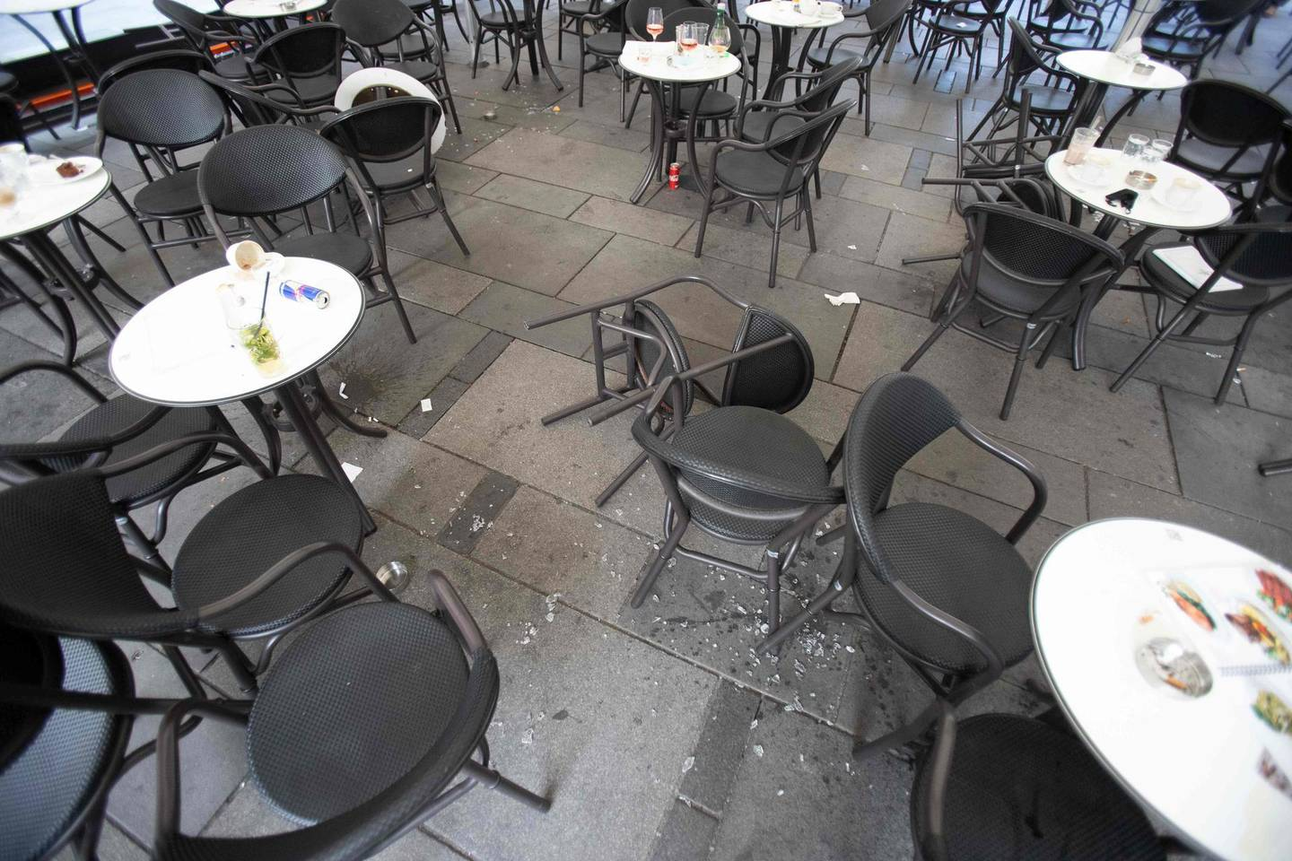 """Broken glass is seen on the ground next to chairs and tables of a cafe near Stephansplatz in Vienna on November 3, 2020, after a shooting at multiple locations across central Vienna. Four people were killed in multiple shootings in Vienna on Monday evening, November 2, 2020, in what Austrian Chancellor Sebastian Kurz described as a """"repulsive terror attack"""". / AFP / ALEX HALADA"""