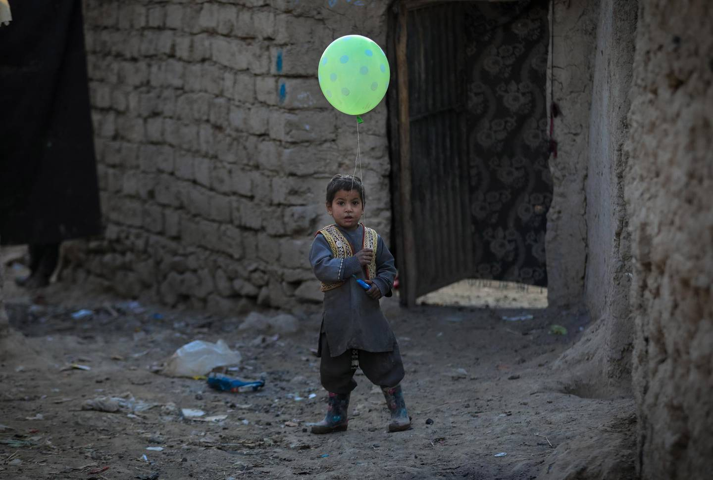 epa08948976 An Afghan internally displaced boy poses for a photograph as he holds a balloon near to a temporary shelter at an Internally Displaced Persons (IDPs) camp on the outskirts of Kabul, Afghanistan on 19 January 2021. Over 18.4 million Afghans including 9.7 million children in Afghanistan desperately need life-saving support, said Save the Children in a statement on 19 January, therefore the NGO is calling for billions of dollars in aid to cope with the challenges.  The NGO says a combination of conflict, poverty, and the Coronavirus pandemic continue to have devastating impacts on the population and continue to fuel humanitarian needs in Afghanistan.  EPA/HEDAYATULLAH AMID