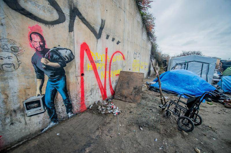 """epa05080943 A tag of the artist Banksy representative Steve Jobs in the camp called 'The Jungle' in the port of Calais, France, 25 December 2015.  By this Banksy tag means that Steve Jobs was also a Syrian migrant son come Holms. He said. """"We are often led to believe that immigration will pump a country's resources, but Steve Jobs was the son of a Syrian immigrant Apple is the most profitable company in the world, it pays more than 7 billion per year in taxes - and it is only because they have left back a young man of Homs """"  EPA/STEPHANIE LECOCQ"""