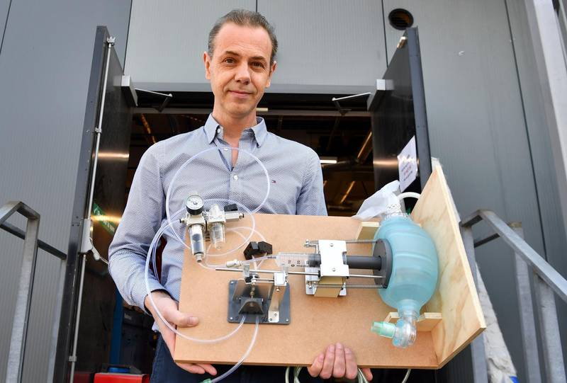 """Nick Grey, the owner of GTech, an independent British company designing and manufacturing cordless home and garden appliances such as vacuum cleaners, floor sweepers, grass trimmers, poses for a photograph with the company's prototype ventilator, at their headquarters in Wardon, near Worcester, west of England on March 24, 2020. When vacuum cleaner manufacturer Nick Grey got an email last weekend from a """"special government adviser"""" urging him to get in touch, he thought it was a hoax. Now he could soon be on the frontline of making thousands of emergency hospital ventilators to help treat future patients of the coronavirus outbreak. """"I wasn't really sure it (the email) was genuine but I looked up the name online. It seemed to check out,"""" he told AFP at his Gtech factory in Worcester, central England.  - TO GO WITH AFP STORY BY William EDWARDS  / AFP / Paul ELLIS / TO GO WITH AFP STORY BY William EDWARDS"""