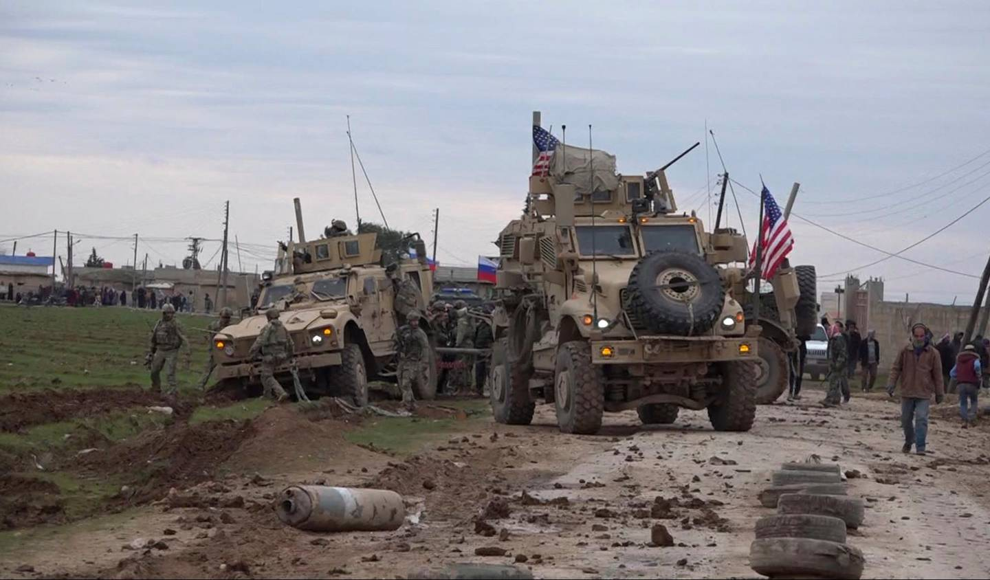 In this frame grab from video taken on Wednesday, Feb. 12, 2020, people and soldiers gather next to an American military convoy stuck in the village of Khirbet Ammu, east of Qamishli city, Syria, Wednesday, Feb. 12, 2020. The Syrian official news agency SANA, said Wednesday, that locals had gathered at an army checkpoint, pelting the U.S. convoy with stones and taking down a U.S. flag flying on a vehicle when troops fired with live ammunition and smoke bombs. (AP Photo)