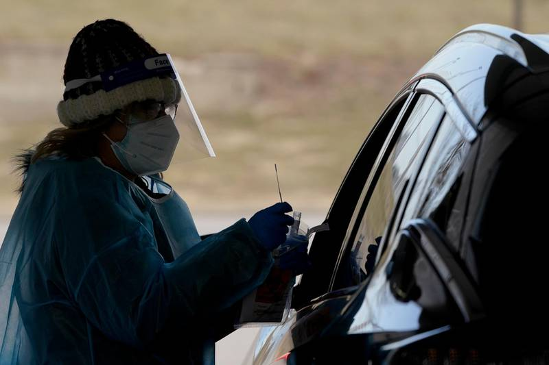 A health care worker prepares to collect a sample from a person at a drive-thru COVID testing site Friday, Dec. 18, 2020 in Olathe, Kan. (AP Photo/Charlie Riedel)