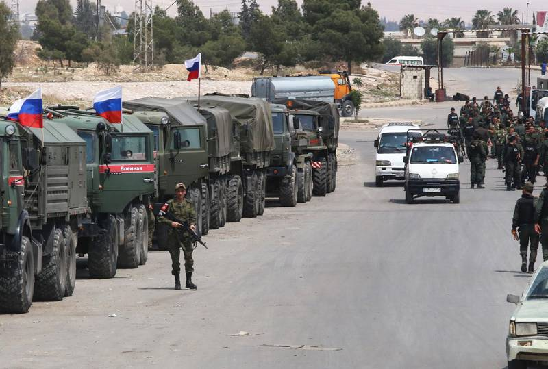 Syrian and Russian soldiers wait at the entrance of the Wafideen Camp for the arrival of buses carrying Jaish al-Islam fighters and their family members evacuated from the Eastern Ghouta town of Douma, on April 12, 2018.  Rebels in Syria's Eastern Ghouta surrendered their heavy weapons and their leader left the enclave, a monitor said, signalling the end of one of the bloodiest assaults of Syria's seven-year war. / AFP PHOTO / Youssef KARWASHAN