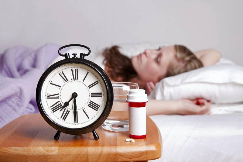 Woman lays sleepless in bed (blurred) with an alarm clock, pills, pill bottle, and water on the nightstand; copy space