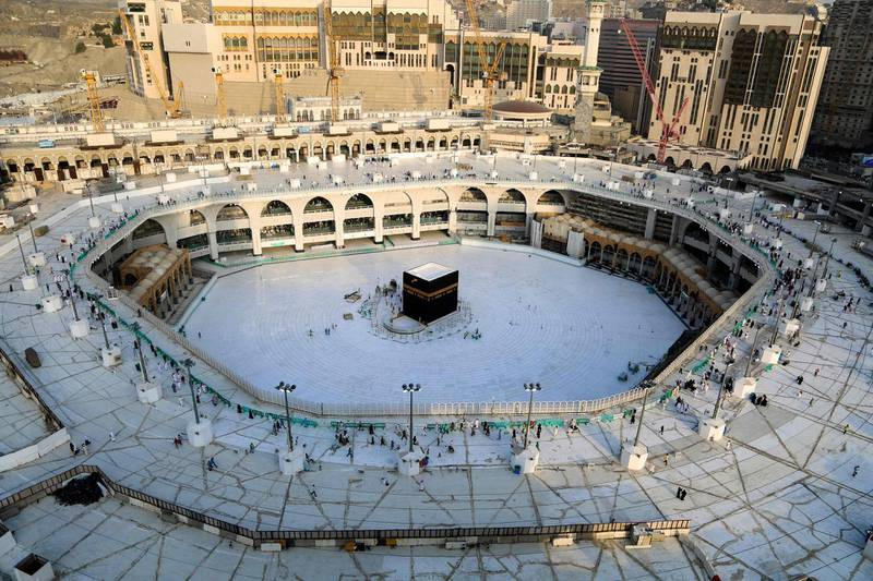 """(FILES) This file photo taken on March 05, 2020 shows the white-tiled area surrounding the Kaaba, inside Mecca's Grand Mosque, empty of worshippers.  Saudi Arabia announced it would hold a """"very limited"""" hajj this year owing to the coronavirus pandemic, with pilgrims already in the kingdom allowed to take part. / AFP / ABDEL GHANI BASHIR"""