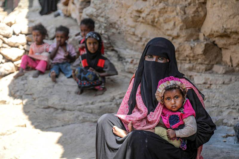 A woman holds a child as she sits near other children outside a cave where a Yemeni family has sought refuge due to poverty and lack of housing, west of the suburbs of Yemen's third-city of Taez on December 2, 2020. (Photo by AHMAD AL-BASHA / AFP)