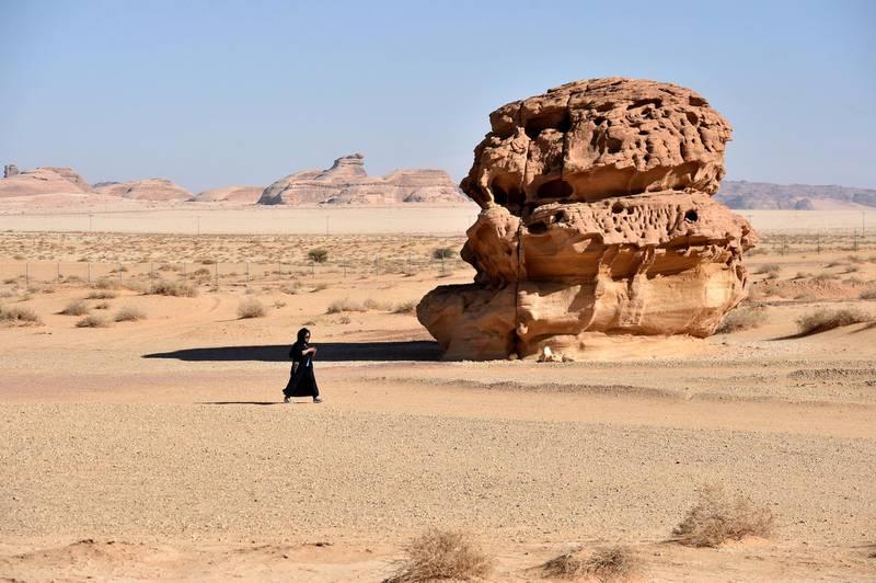 A picture taken on January 4, 2019, shows a woman walking past rose-coloured sandstone in Madain Saleh, a UNESCO World Heritage site, near Saudi Arabia's northwestern town of al-Ula. (Photo by Fayez Nureldine / AFP)