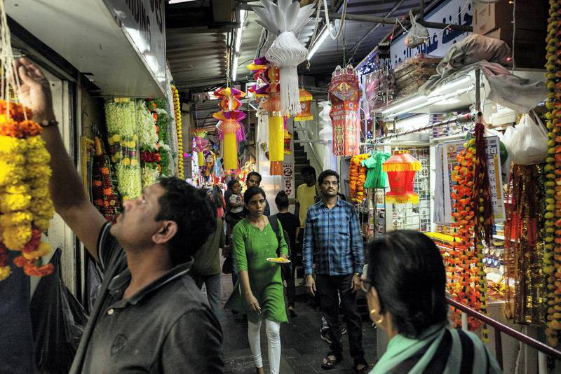 """DUBAI, UNITED ARAB EMIRATES. 24 OCTOBER 2019. Worshippers pass by Hindu shops while on their way to the Hindu Temple. As the Hindu Festival of Diwali starts in the UAE, devotees flok to the Hindu Temple in Bur Dubai to worship. Adjacent to the Temple is what is commonly refered to """"Hindi Lane"""", a small corridor of shops selling flowers, offerings and general items for Hindu ceremonies. Diwali, Deepavali or Dipavali is a four-to-five day-long festival of lights, which is celebrated by Hindus, Jains, Sikhs and some Buddhists every autumn in the northern hemisphere. (Photo: Antonie Robertson/The National) Journalist: None. Section: National."""
