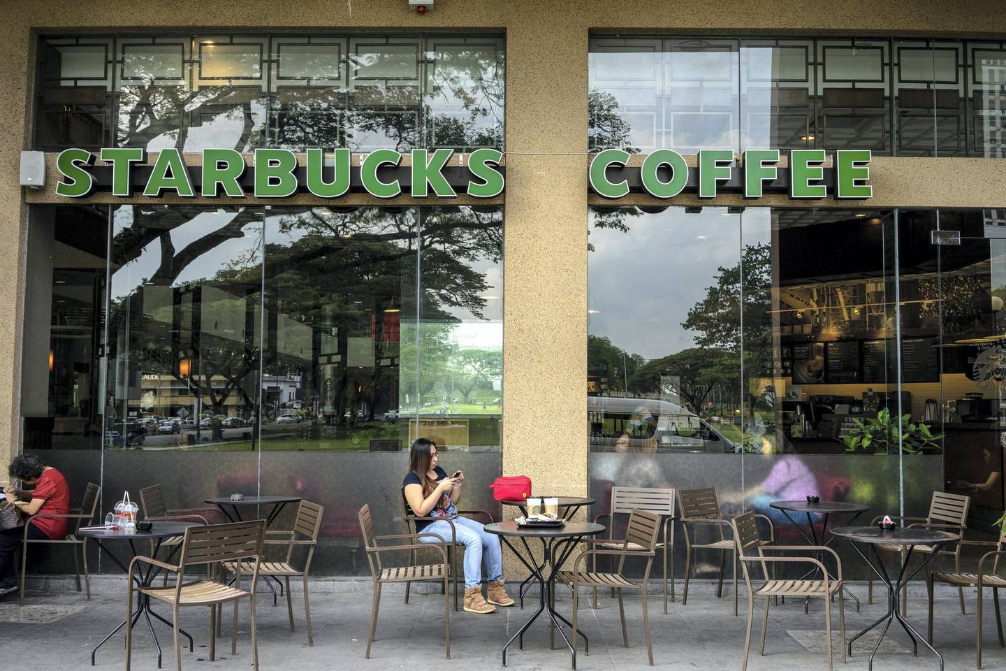 Customers sit inside and outside a Starbucks Corp. coffee shop at Parksons Mall in Kuching, Sarawak, Malaysia, on Wednesday, April 13, 2016. Separated from peninsular Malaysia by the South China Sea, Sarawak was the country's third-largest state or territory contributor to gross domestic product in 2015, accounting for an estimated 10.6 percent of output. Photographer: Sanjit Das/Bloomberg