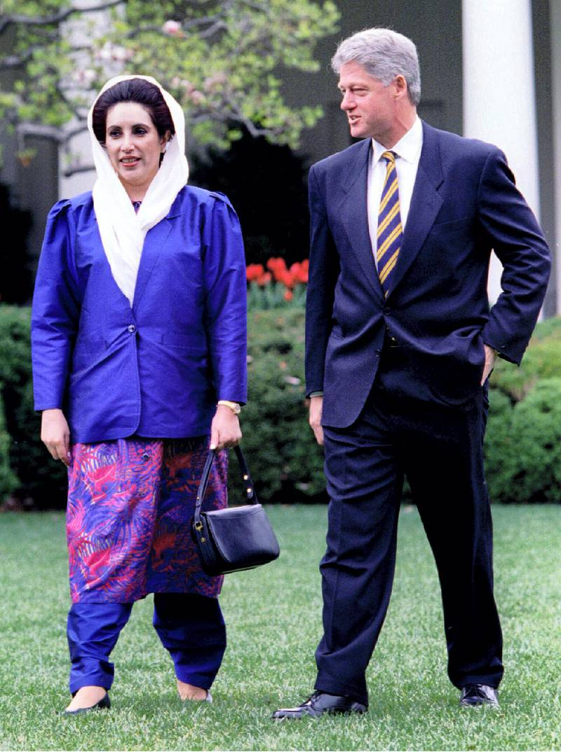 President Clinton (R) and visiting Pakistani Prime Minister Benazir Bhutto walk through the Rose Garden on their way to lunch April 11 at the White House. Earlier, Clinton met with Bhutto in a bid to solve a dispute over $1.4 billion in military hardware, including F 16 jets
