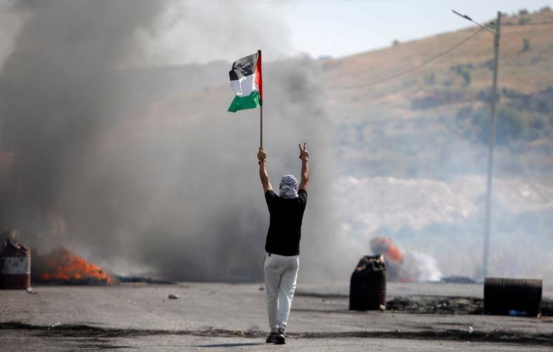 A demonstrator holding a Palestinian flag gestures during a protest over tension in Jerusalem and Israel-Gaza escalation, near Hawara checkpoint near Nablus in the Israeli-occupied West Bank, May 14, 2021. REUTERS/Raneen Sawafta
