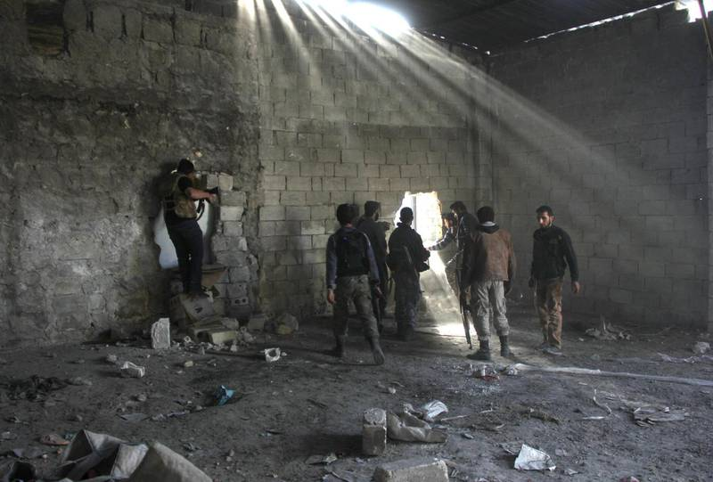 Rebel fighters are pictured inside a building during clashes with pro-government forces in the Sheikh al-Said neighbourhood of Syria's northern city of Aleppo on November 28, 2013. More than 120,000 people have been killed since the beginning of the conflict in Syria in March 2011, and millions of Syrians have been displaced from their homes. AFP PHOTO/ZAKARIYA AL-KAFI (Photo by Zakaria ABDELKAFI / AFP)