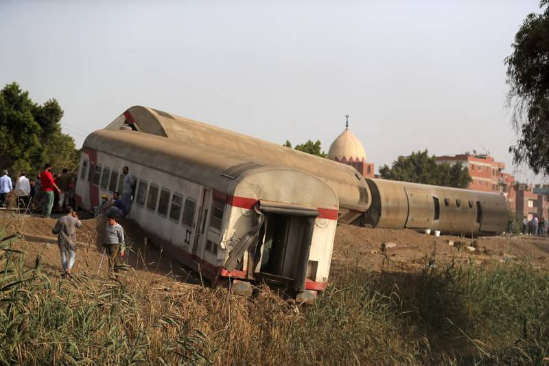 People gather at the site where train carriages derailed in Qalioubia province, north of Cairo, Egypt April 18, 2021. REUTERS/Mohamed Abd El Ghany