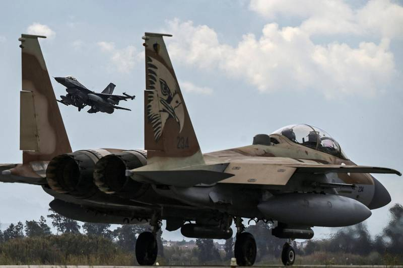 """A Hellenic Air Force F-16 jet takes off behind an Israeli F-15 from the military airport of Andravida, southern Greece, on April 19, 2021. - Led by the Hellenic Air Force, """"INIOCHOS 2021"""" multinational aviation exercise is underway over the entirety of Greece's FIR. (Photo by ARIS MESSINIS / AFP)"""