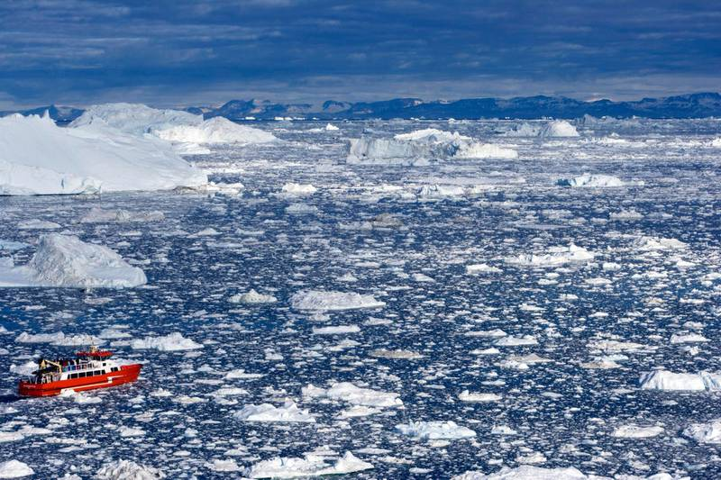 Ilulissat, Greenland --- Greenland, Ilulissat, UNESCO World Heritage Site Icefjord. A tourist boat navigates its way through the labyrinth of icebergs in the bay in front of Ilulissat. --- Image by © Mark Hannaford/JAI/Corbis