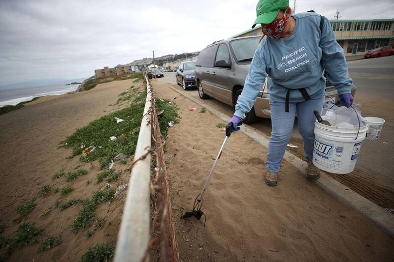 PACIFICA, CALIFORNIA - APRIL 3: Terri Brown, a volunteer with Pacific Beach Coalition, uses a grabber tool to pick up a discarded surgical mask while picking up trash near Pacifica Esplanade Beach on April 3, 2021 in Pacifica, California. Concerns are growing over discarded COVID-19 related used personal protective equipment (PPE) that is littering streets and waterways since it contains microplastics that don't break down easily and could take hundreds of years to decompose. In September of 2020, the California Coastal Commission created a new category for masks and gloves for its coastal cleanups.   Justin Sullivan/Getty Images/AFP == FOR NEWSPAPERS, INTERNET, TELCOS & TELEVISION USE ONLY ==