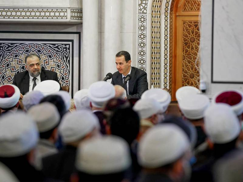 """This handout picture released by the Syrian Presidency Facebook page on December 7, 2020, shows Syrian President Bashar al-Assad delivering a speech, flanked by Minister of Awqaf (Religious Endowments) Mohammad Abdul-Sattar al-Sayyed (L), during the periodic meeting held by the Ministry of Endowments at Al-Othman Mosque in the .   - XGTY / RESTRICTED TO EDITORIAL USE - MANDATORY CREDIT """"AFP PHOTO / Syrian Presidency Facebook page """" - NO MARKETING NO ADVERTISING CAMPAIGNS - DISTRIBUTED AS A SERVICE TO CLIENTS  / AFP / - / XGTY / RESTRICTED TO EDITORIAL USE - MANDATORY CREDIT """"AFP PHOTO / Syrian Presidency Facebook page """" - NO MARKETING NO ADVERTISING CAMPAIGNS - DISTRIBUTED AS A SERVICE TO CLIENTS"""
