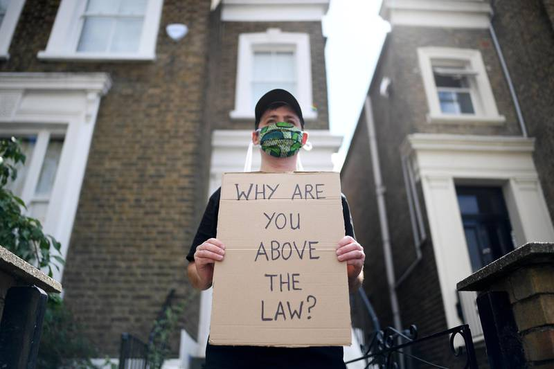 LONDON, ENGLAND - MAY 24: A protester holds up a placard which reads 'Why are you above the law?' outside the home of Dominic Cummings, Chief Advisor to Prime Minister Boris Johnson, on May 24, 2020 in London, England. On March 31st 2020 Downing Street confirmed to journalists that Dominic Cummings was self-isolating with COVID-19 symptoms at his home in North London. Durham police have confirmed that he was actually hundreds of miles away at his parent's house in the city. (Photo by Peter Summers/Getty Images)
