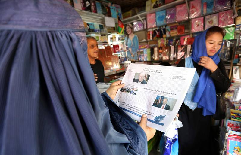 """A woman reads a local newspaper displaying a photo of U.S. President Donald Trump on its front in Kabul, Afghanistan, Tuesday, Aug. 22, 2017. Reversing his past calls for a speedy exit, Trump recommitted the United States to the 16-year-old war in Afghanistan Monday night, declaring U.S. troops must """"fight to win."""" (AP Photo/Rahmat Gul)"""