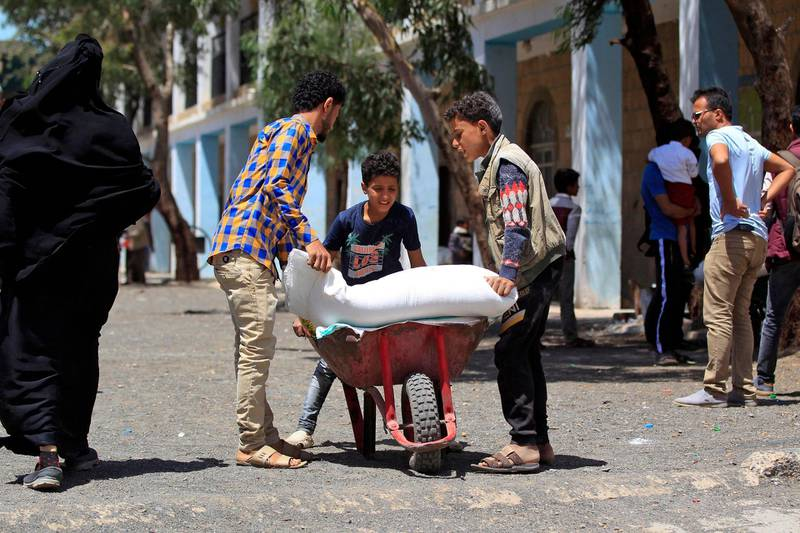 Yemenis receive humanitarian aid provided by the World Food Programme (WFP) in the Yemeni capital Sanaa on June 1, 2021. / AFP / MOHAMMED HUWAIS