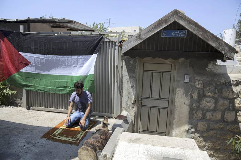 A man is seen praying by a Palestinian flag hung on a home next to the house of the  Shamasneh family during a support protest  Friday noon prayer in the East Jerusalem neighborhood of Sheik Jarrah on August 11,2017.  When the Shamasne family first moved into their home  in the 1960s, East Jerusalem was controlled by Jordan and their monthly rent was paid to  Jordanian authorities but since  Israel annexed East Jerusalem in 1967, the Shamasne family has paid their rent to Israel's general custodian in order to remain in the building. The family claims that their payments were suddenly rejected in 2009 , and they were informed that the property had been claimed by Israeli Jews whose ancestors had lived there decades previously.Although the family has spent years fighting to remain in the home , the Israeli high court has ruled that the family must evacuate the home before August 9. (Photo by Heidi Levine for The National).