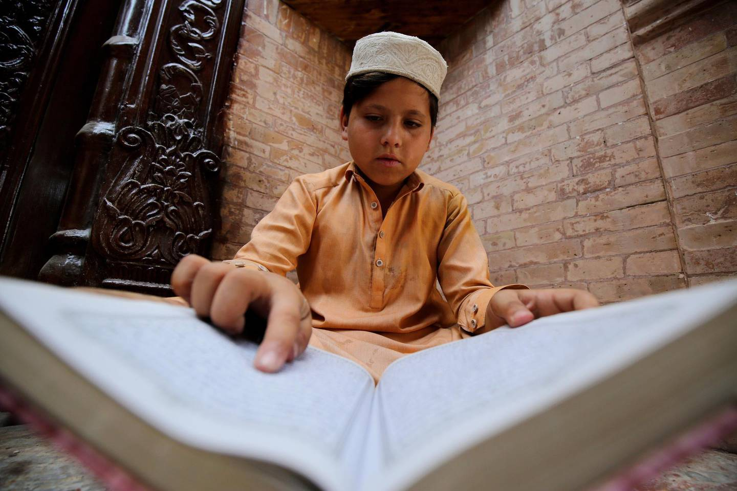 epa09169550 A Pakistani Muslim boy reads verses from the holy Koran at a Mosque during the fasting month of Ramadan, amid the coronavirus pandemic in Peshawar, Pakistan, 30 April 2021. Muslims around the world celebrate the holy month of Ramadan by praying during the night time and abstaining from eating, drinking, and sexual acts during the period between sunrise and sunset. Ramadan is the ninth month in the Islamic calendar and it is believed that the revelation of the first verse in Koran was during its last 10 nights.  EPA/BILAWAL ARBAB