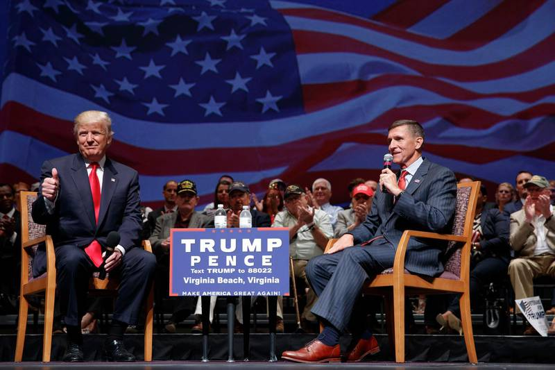 """FILE - Then-presidential candidate Donald Trump gives a thumbs up as he speaks with retired Lt. Gen. Michael Flynn during a town hall, Tuesday, Sept. 6, 2016, in Virginia Beach, Va. President Donald Trump has pardoned Michael Flynn, taking direct aim in the final days of his administration at a Russia investigation that he has long insisted was motivated by political bias. Trump announced the pardon on Wednesday, Nov. 25, 2020 calling it his """"Great Honor."""" (AP Photo/Evan Vucci, file)"""