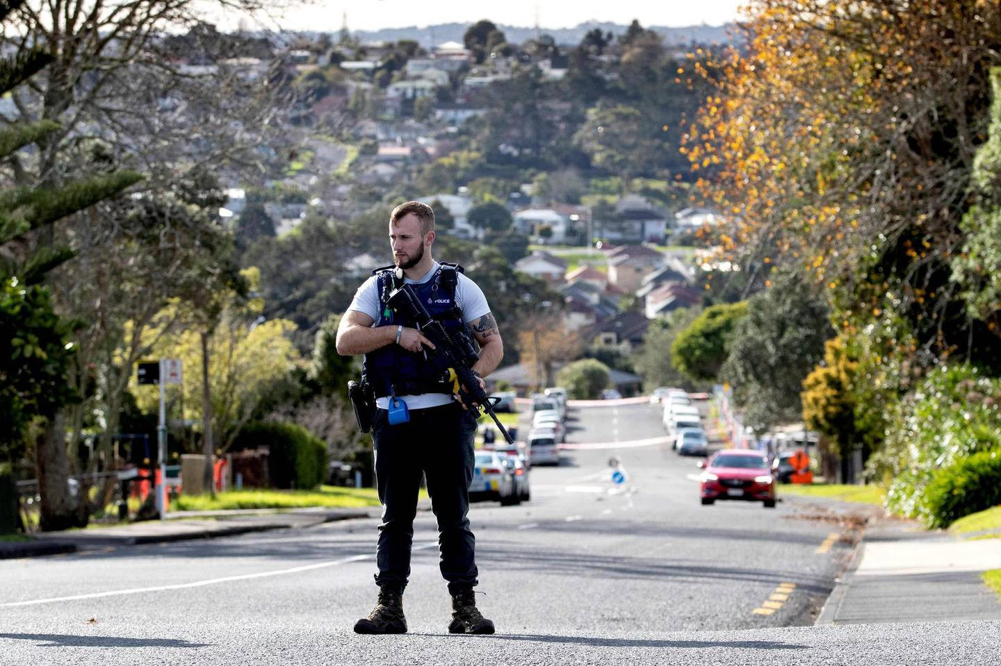 """A police officer cordons off an area after a shooting incident in a residential neighbourhood in Auckland on June 19, 2020. An unarmed New Zealand police officer was shot dead on an Auckland street on June 19 in a rare fatal attack that Prime Minister Jacinda Ardern described as """"devastating"""". / AFP / GREG BOWKER"""