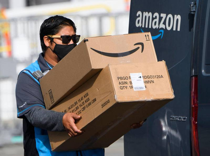 (FILES) In this file photo taken on February 02, 2021, an Amazon delivery driver carries boxes into a van outside of a distribution facility in Hawthorne, California. A week of blockbuster earnings reports from Big Tech culminates Thursday with Amazon revealing profits from pandemic-revved online shopping and growing reliance on internet-hosted services. The e-commerce colossus is among the internet giants whose businesses thrived as precautions against Covid-19 led people around the world to go online for work, school, shopping and socializing. / AFP / Patrick T. FALLON