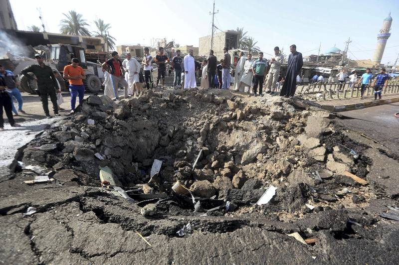 Iraqi men look at a crater left by a massive suicide car bomb attack carried out the previous day by the Islamic State group in the predominantly Shiite town of Khan Bani Saad, 20 km north of Baghdad, on July 18, 2015. The suicide attack by the IS group was one of the deadliest since it took over swathes of Iraq last year and came as the country marked Eid al-Fitr, the Muslim feast that ends the fasting month of Ramadan. AFP PHOTO / AHMAD AL-RUBAYE (Photo by AHMAD AL-RUBAYE / AFP)