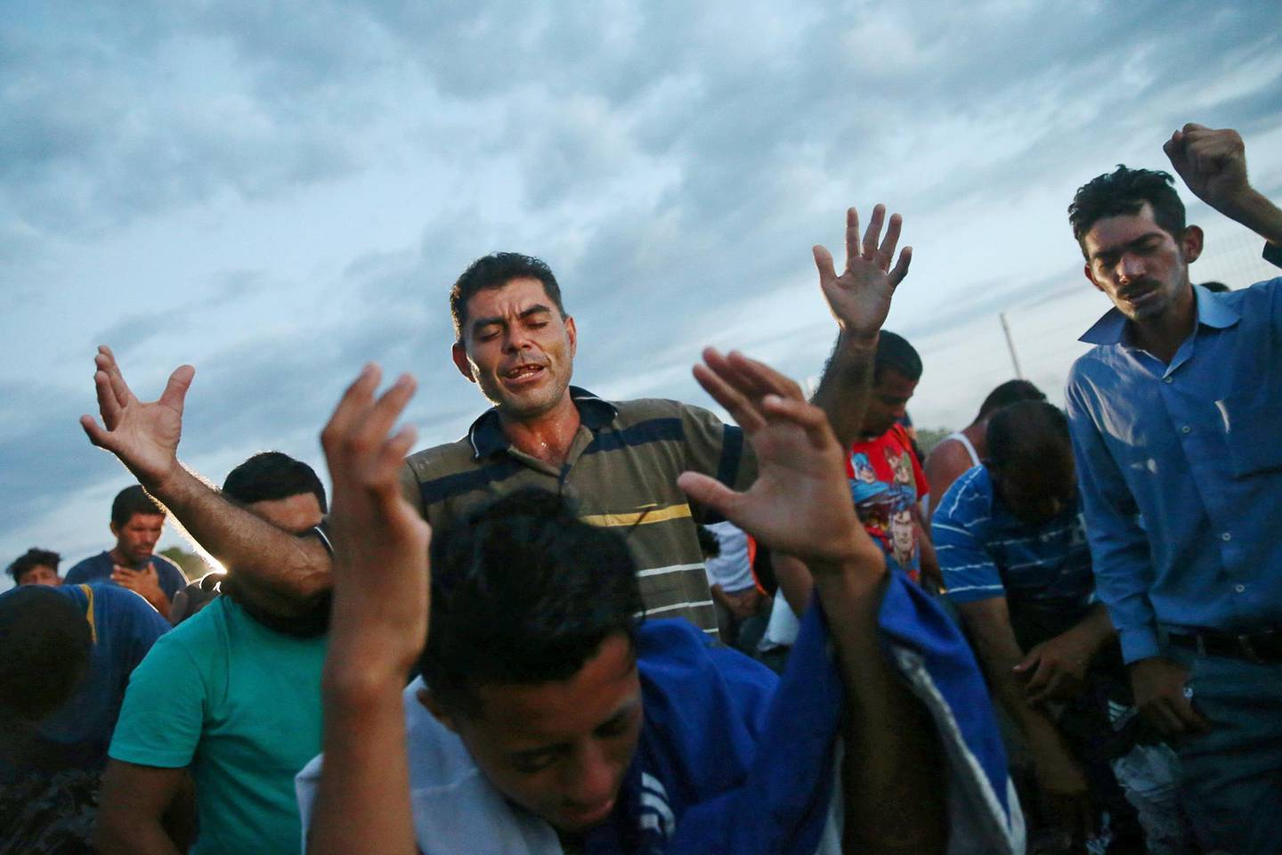 Central American migrants, part of a caravan trying to reach the U.S., pray as they wait on the bridge that connects Mexico and Guatemala to cross into Mexico to continue their trip, in Ciudad Hidalgo, Mexico October 22, 2018. REUTERS/Edgard Garrido