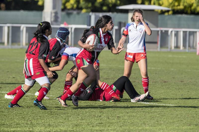 ABU DHABI, UNITED ARAB EMIRATES. 29 November 2018. First day of the Rugby Sevens Tournament. Al Maha School girls team of all Emirati Female Players (Red and black colours). (Photo: Antonie Robertson/The National) Journalist: Paul Radley. Section: Sport.