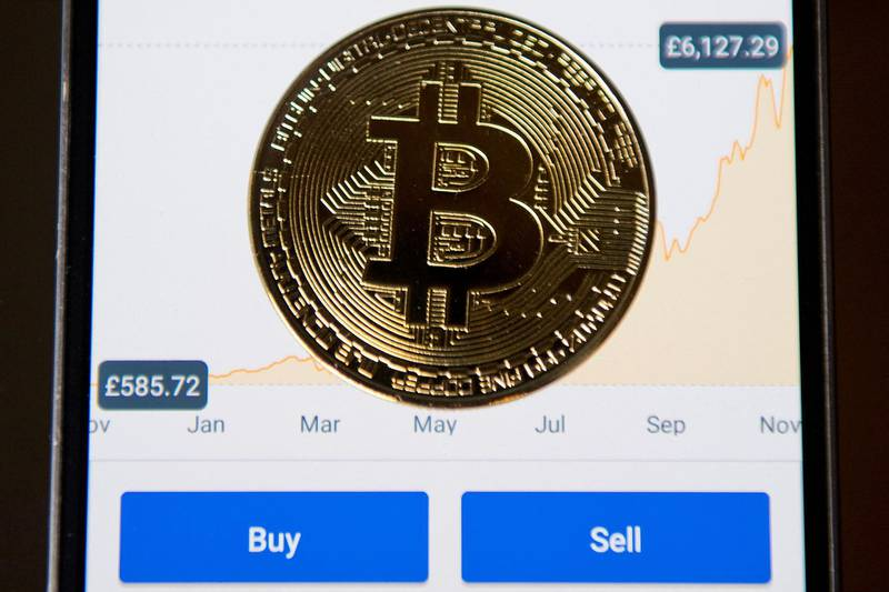 (FILES) In this file photo taken on November 21, 2017, a gold plated souvenir Bitcoin coin is arranged for a photograph on a smart phone on an app for the digital asset broker, Coinbase, in London. Coinbase, an exchange for bitcoin and other cryptocurrencies, filed papers on February 25, 2021, to become publicly traded in the latest sign of the rise of digital currencies. / AFP / Justin TALLIS