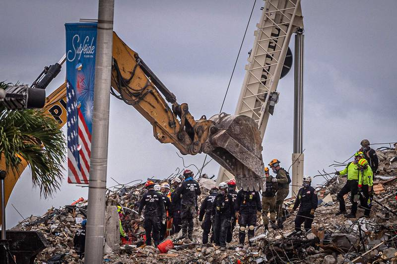 Search and rescue teams look for possible survivors in the rubble of the partially collapsed 12-story Champlain Towers South building can be seen on June 28, 2021 in Surfside, Florida. Questions mounted Monday about how a residential building in the Miami area could have collapsed so quickly and violently last week, as the death toll rose to 11 with 150 still unaccounted for, and desperate families feared the worst. / AFP / Giorgio Viera