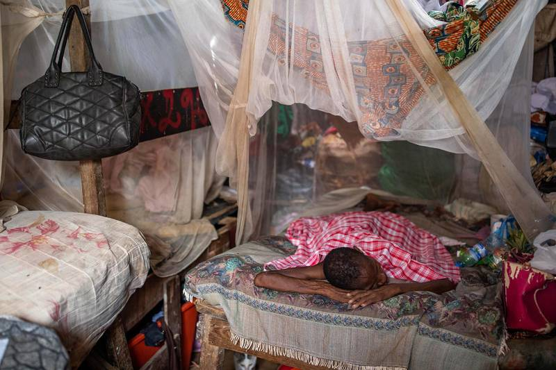 """FOR MALARIA / SMALPOX GALLERY LUANDA, ANGOLA - JANUARY 27: A woman, suffering from malaria, rests on her families bed inside the Povoado slum on January 27, 2020 in Luanda, Angola. Eight families live in this room, each with one bed. In June 2013, 3000 families were evicted from a shanty town called Areia Branca, forcibly removed without warning by police and local officials.  500 families have relocated to a former waste dump known as Povoado, where two sewage channels flow through their encampment and diseases such as meningitis, tuberculosis and malaria are common. Residents  have raised their beds high off the ground as during storms and particularly high tides their houses flood with sewage from the nearby lagoon. The Luanda Leaks investigation suggests that Isabel dos Santos's company,  Urbinveste, would benefit from the redevelopment of Areia Branca, claims she denies. Dos Santos said her plans, which were backed by her father, did not require evictions. She also insists her business relationship with her father's government was """"arm's length"""", and that she was """"not financed by any state money or funds"""". Businesswoman Isabel dos Santos is the daughter of the former President of Angola - Jose Eduardo dos Santos. Forbes Magazine put her fortune at $2.1billion making her the richest woman in Africa. How she made her fortune has come under scrutiny as international media using information from the Luanda Leaks have revealed how, during his presidency, her father sanctioned her acquisition of stakes in Angolan industries including banking, diamonds, oil and telecoms. In December 2019 the Angolan Courts froze Dos Santos's stakes in Angolan companies as it bought a case against her regarding funds owed to the state oil firm. (Photo by Luke Dray/Getty Images)"""