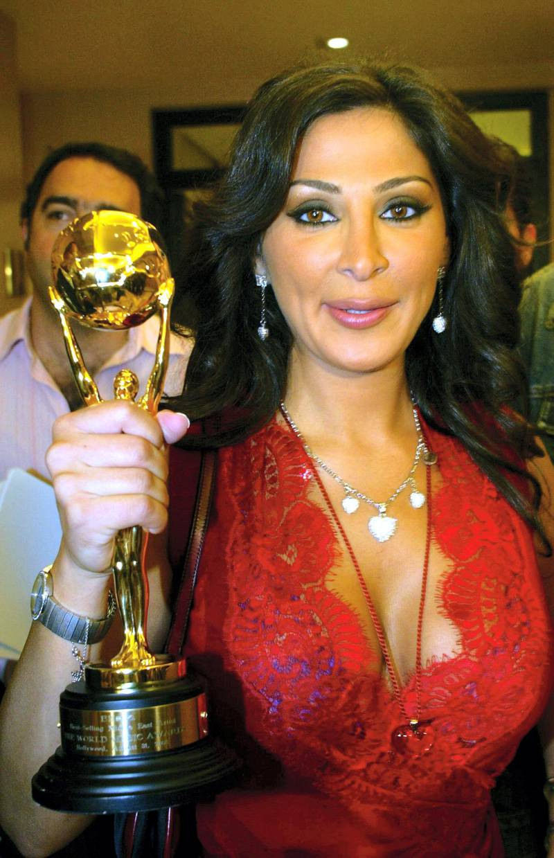 """Lebanese pop star Elissa displays her World Music Award as the best Arab singer and the best-selling artist in the Middle East and North Africa for her album """"Ahla Dunia"""", during a press conference in Beirut late 02 September 2005. Elissa received her award on August 31 at the 2005 World Music Awards show held at the Kodak Theater in Hollywood. AFP PHOTO/ANWAR AMRO (Photo by ANWAR AMRO / AFP)"""