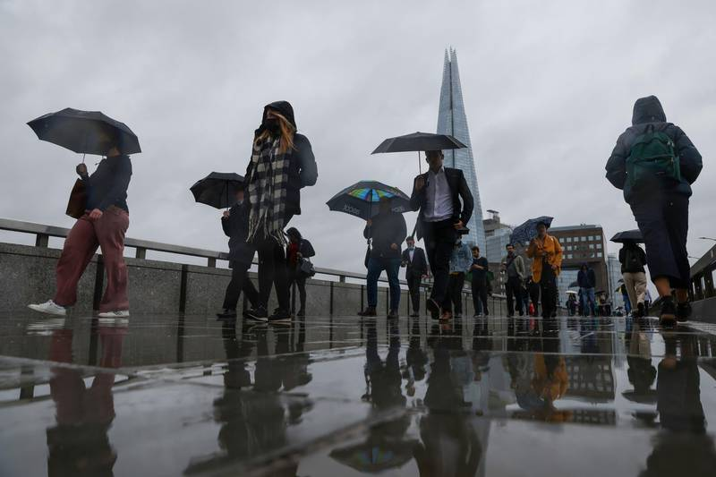 Commuters use their umbrellas to shelter from the rain as they cross London Bridge in London, U.K., on Monday, June 21, 2021. Almost half of London companies whose staff can work from home expect them to do so up to five days a week after the pandemic finishes, and smaller businesses are more likely than larger ones to move ahead with remote working. Photographer: Hollie Adams/Bloomberg
