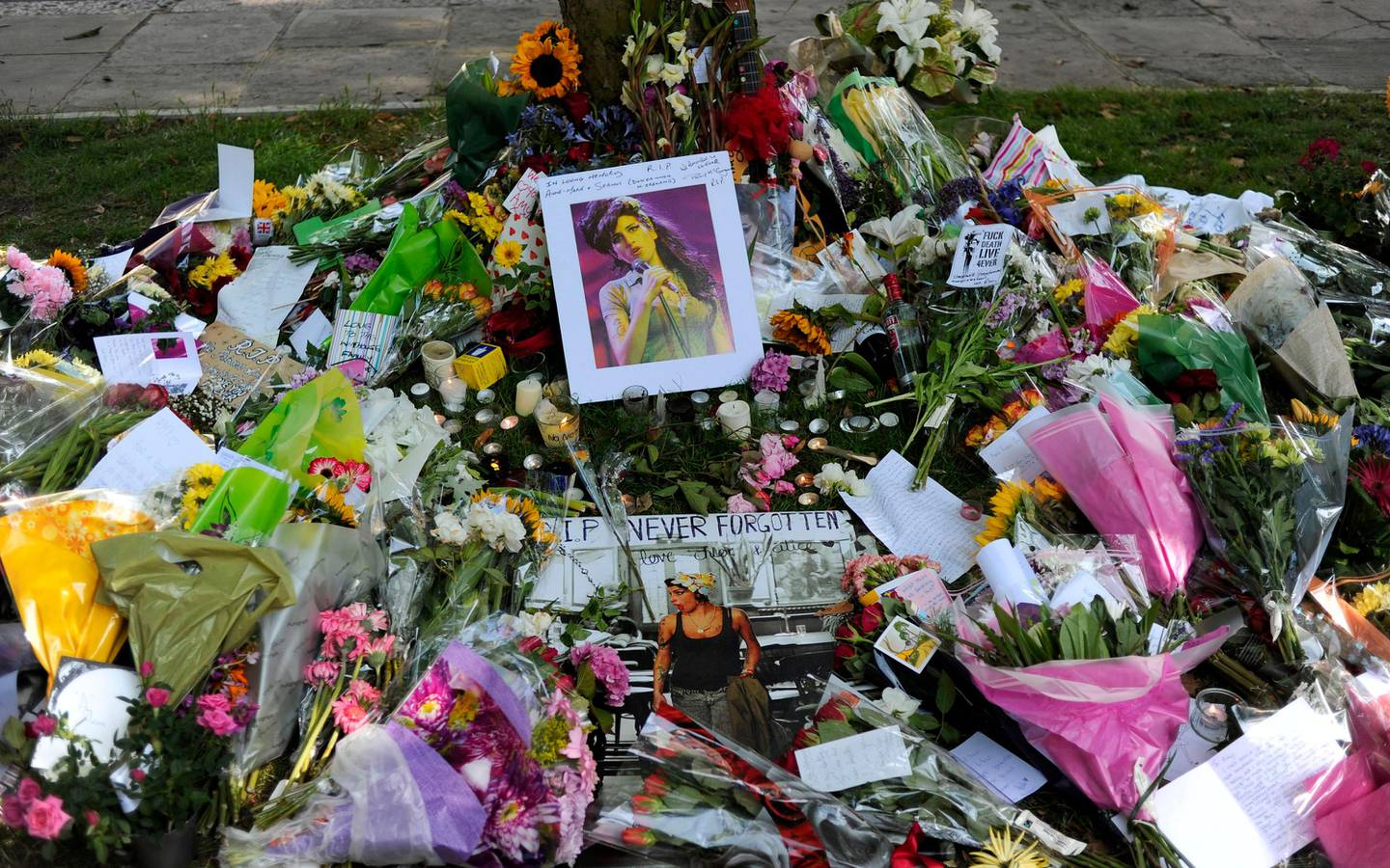 Flowers, pictures and messages are left in tribute to late soul music and pop star Amy Winehouse, near the house in north London where her body was found the previous day, on July 24, 2011. Soon after the 27-year-old songstress's death was announced on July 23, fans started gathering in Camden Square, north London, to bid farewell to a star whose songs often reflected her tempestuous lifestyle. AFP PHOTO/CARL COURT