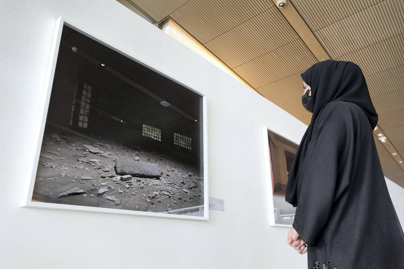 Sharjah, United Arab Emirates - December 10, 2020: News. Arts. A visitor looks at a picture as part of The Ashes series. Opening of the House of Wisdom, a high tech new library. Thursday, December 10th, 2020 in Sharjah. Chris Whiteoak / The National