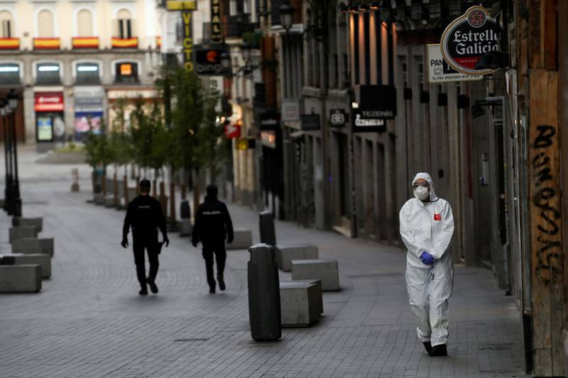 A medical worker in a protective suit walks past police officers patrolling a deserted street during the coronavirus disease (COVID-19) outbreak in Madrid, Spain March 22, 2020. REUTERS/Susana Vera