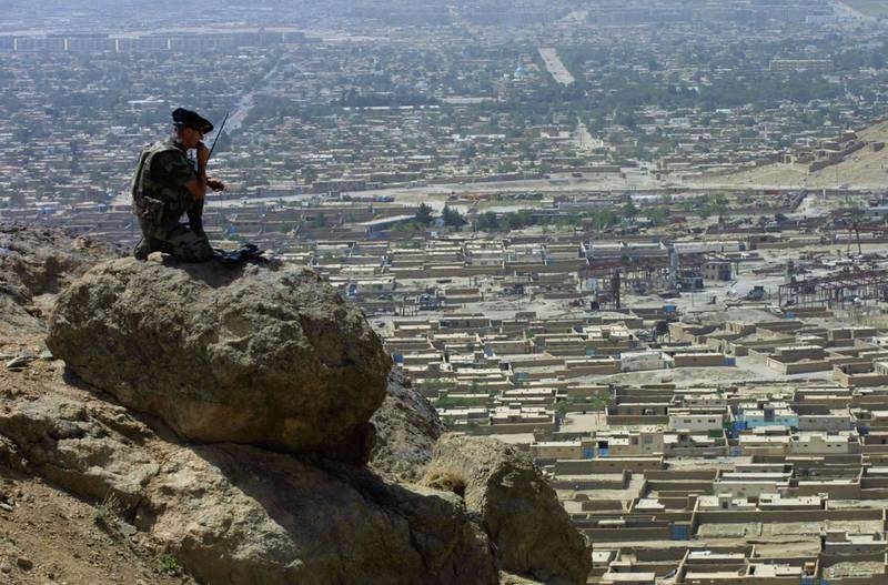 KABUL, AFGHANISTAN - AUGUST 3:  A French soldier from the 7th Mountain Regiment, part of the International Security and Assistance Force (ISAF) stands on a boulder overlooking Kabul during a patrol August 3, 2002 in Afghanistan. The ISAF has been patrolling Kabul since January 2002, working with the government and a new police force to prevent the violence and lawlessness that threatened to engulf the city after a U.S.-led coalition forced the Taliban from power.  (Photo by Natalie Behring-Chisholm/Getty Images)