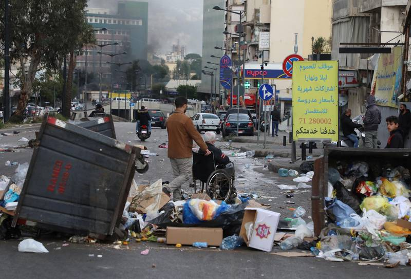 A man pushes an elderly on a wheelchair near garbage bins placed by demonstrators to block a road, during a protest against the fall in Lebanese pound currency and mounting economic hardships, in Beirut, Lebanon March 16, 2021. REUTERS/Mohamed Azakir